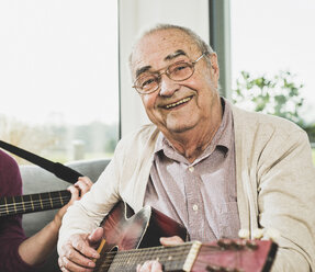 Portrait of senior man playing guitar - UUF006633