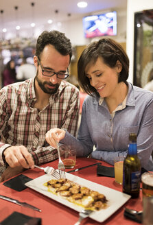 Couple eating cooked octopus in a Spanish bar - JASF000383