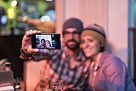 Couple in a winter terrace bar taking a selfie - JASF000386