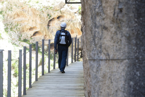 Spain, Ardales, back view of tourist walking along The King's Little Pathway - KIJ000163
