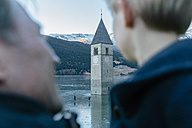 Italy, Venosta Valley, Father and son looking at sunken spire in frozen Lago di Resia - MFF002628