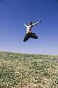 Happy woman jumping on a meadow in front of blue sky - ABZF000195