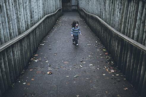 Boy walking on path between high wooden poles - BOYF000096