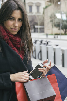 Spain, portrait of young woman with smartphone and shopping bags - ABZF000197