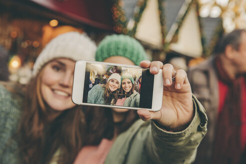 Two happy women taking a selfie on the Christmas Market - MFF002645