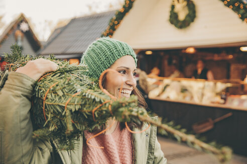 Happy woman with a wrapped-up tree walking over the Christmas Market - MFF002648