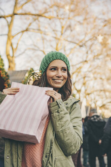 Happy woman holding a gift bag on the Christmas Market - MFF002660