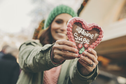 Woman holding up a gingerbread heart on the Christmas Market - MFF002669