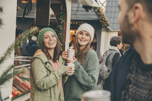 Happy friends having a hot punch on the Christmas Market - MFF002678