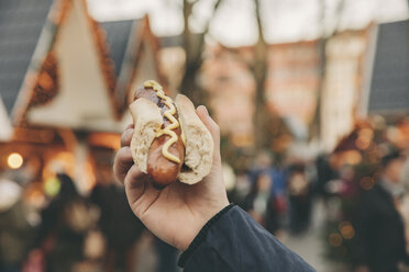 Hand of a man holding a Bratwurst on the Christmas Market - MFF002681