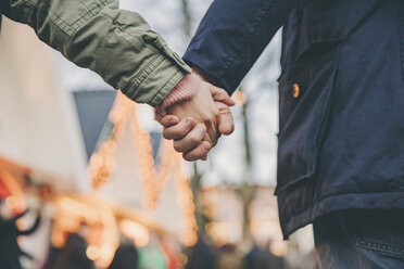 Close-up of couple holding hands on the Christmas Market - MFF002690