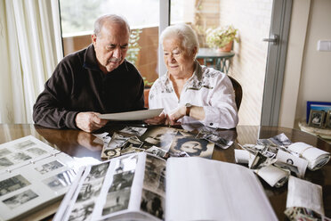 Senior couple watching their  old photographies and photo albums at home - GEMF000720