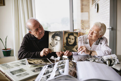 Senior couple showing old pictures of themselves - GEMF000723