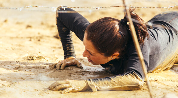Participant in extreme obstacle race crawling under barbed wire - MGOF001384