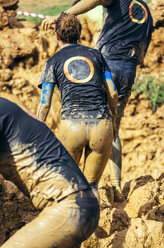 Participants in extreme obstacle race, running through mud - MGOF001387
