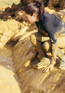 Participants in extreme obstacle race, running through mud - MGOF001390