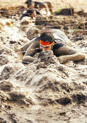 Participant in extreme obstacle race crawling under barbed wire - MGOF001393
