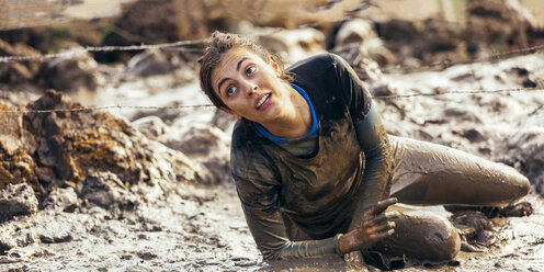 Participant in extreme obstacle race crawling under barbed wire - MGOF001396