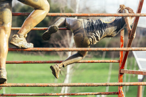 Participants in extreme obstacle race climbing over hurdle - MGOF001402