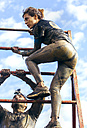 Participants in extreme obstacle race climbing over hurdle - MGOF001405