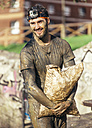 Participant in extreme obstacle race carrying sandbags - MGOF001408