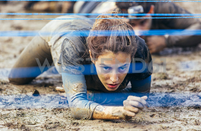 Participants in extreme obstacle race crawling under electric wire - MGOF001411 - Marco Govel/Westend61