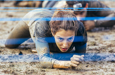 Participants in extreme obstacle race crawling under electric wire - MGOF001411