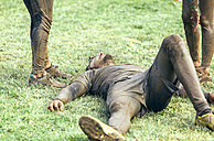 Participant in extreme obstacle race lying exhaustedly on grass - MGOF001414