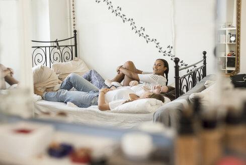 Three teenage girls lying on bed - OJF000093