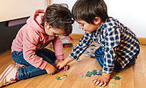 Boy and girl doing a jigsaw on the floor together - MGOF001418