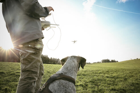 Man on a meadow flying drone while his dog watching - REAF000021