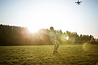 Man on a meadow flying drone - REAF000024