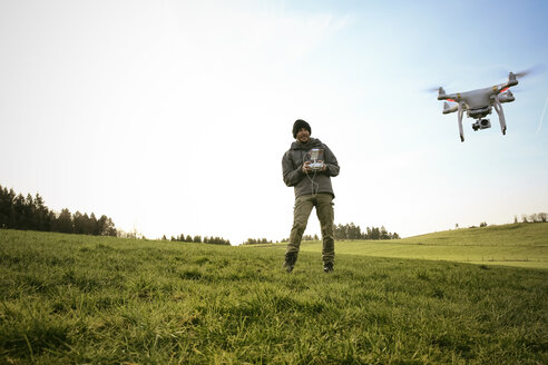 Man on a meadow flying drone while his dog watching - REAF000030
