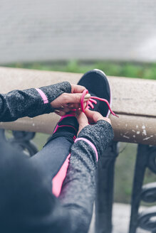 Woman tying shoelaces of pink and black sneakers - DAPF000034