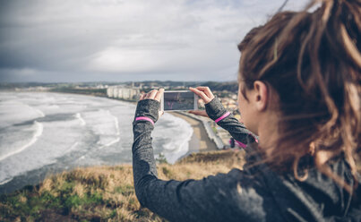 Mid adult sportive woman taking picture with smart phone - DAPF000043