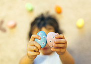 Girl's hands holding two painted Easter eggs - MGOF001424