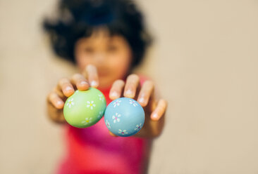 Girl's hands holding two painted Easter eggs - MGOF001427