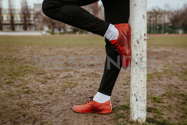 Legs of man leaning against soccer goalpost - ZEDF000056