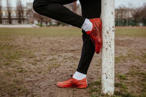 Legs of man leaning against soccer goalpost - ZEDF000056