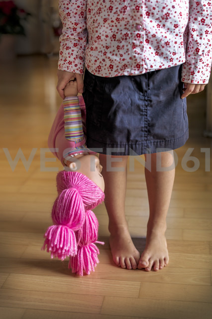 Low section of girl standing on wooden floor holding a doll - EJWF000767 - EJW/Westend61