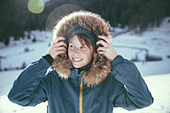 Italy, Val Venosta, Slingia, smiling woman with fur hood in winter landscape - MFF002718