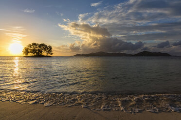 Seychelles, La Digue, Anse Source D'Argent, Praslin Island in the background, small island with trees at sunset - FOF008428