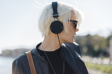 Profile of blond woman wearing sunglasses listening music with headphones - GIOF000727