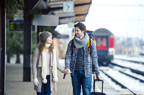 Smiling young couple on station platform - HAPF000199