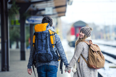 Young couple hand in hand on station platform - HAPF000202