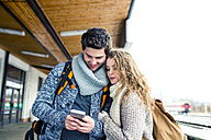 Young couple on station platform looking at cell phone - HAPF000205