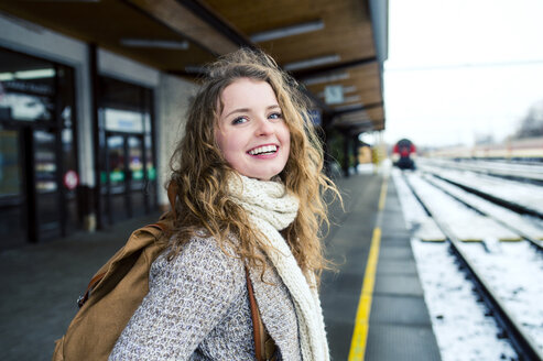 Smiling teenage girl on station platform - HAPF000208