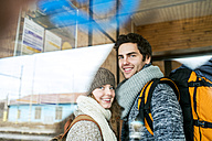 Portrait of smiling young couple at train station - HAPF000211