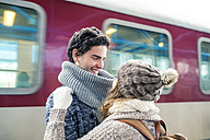 Happy young couple in front of train - HAPF000214