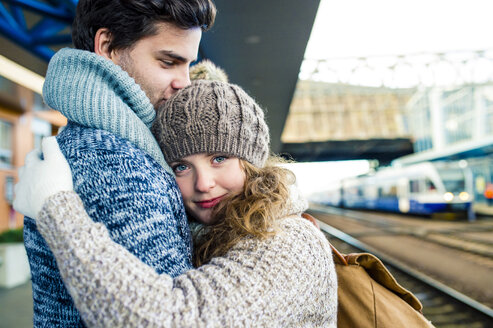 Young couple embracing on station platform - HAPF000217